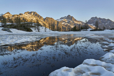 IBXRFA04784432 Mont Avic reflected in Vallette lake, melting snow and ice, Mont Avic Natural Park, Aosta Valley, Italy, Europe