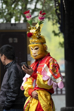 CH11830AW Asia, China, Peoples Republic, Chinese,Sichuan Province, Chengdu, Du Jiang Yan City, Monkey god on phone
