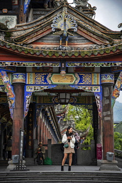 CH11833AW Asia, China, Peoples Republic, Chinese,Sichuan Province, Chengdu, Du Jiang Yan City, girl standing under a covered bridge