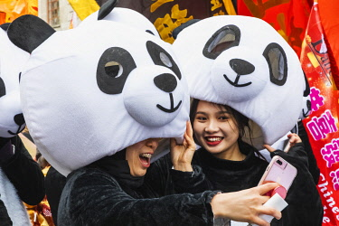 TPX69787 England, London, Chinatown, Chinese New Year Parade, Parade Participants Dressed in Panda Costume Taking  Selfie Photo