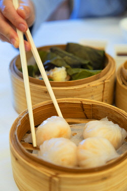 CH11844AW Woman eating dim sum at Maxim�s Palace restaurant, Central, Hong Kong Island, Hong Kong (MR)