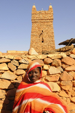 IBLKEL01786030 Woman with scarf in front of Chinguetti Mosque, Chinguetti, Mauritania, northwestern Africa, Africa