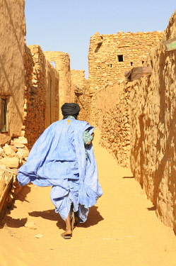 IBLKEL01786040 Man walking through the sandy lanes of the town of Chinguetti, Mauritania, northwestern Africa, Africa