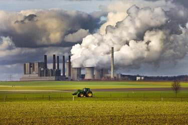 IBLSZI04845831 Tractor on a field in front of the steaming lignite-fired power station Frimmersdorf, Grevenbroich, Rhineland lignite mining area, coal phase-out, North Rhine-Westphalia, Germany, Europe