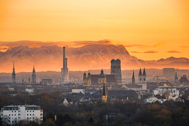 IBXMMW04860093 View over Munich with Church of Our Lady, Theatine Church, Ludwigskirche, behind Zugspitze at sunset, Munich, Bavaria, Germany, Europe