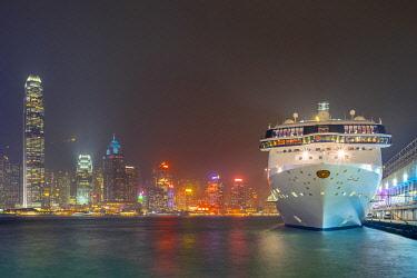 CH11952AW Star Cruises cruiseliner at Ocean Terminal cruise terminal and buildings on Hong Kong Island at night, Tsim Sha Tsui, Kowloon, Hong Kong, China