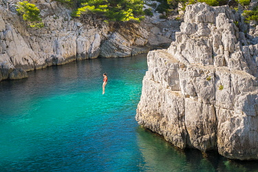 FRA11163AW Young girl jumping from a rock in the Calanque de Sugiton, Parc National des Calanques, Bouches-du-Rhône, Provence-Alpes-Côte d'Azur, France