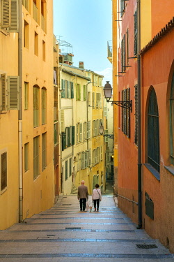 FRA11169AW Two people walking down stairs between colorful buildings, Vieille Ville (old town), Nice, Alpes-Maritimes, Provence-Alpes-Côte d'Azur, France.