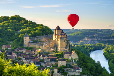 Hot-air balloon over Chateau de Castelnaud castle and Dordogne River valley in late afternoon, Castelnaud-la-Chapelle, Dordogne Department, Aquitaine, France