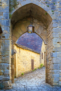 FRA11258AW Stone arched passage along medieval alley in Beynac-et-Cazenac, Dordogne Department, Aquitaine, France