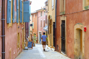 FRA11302AW French man walking through streets of Roussillon carrying a baguette, Vaucluse, Provence-Alpes-Côte d'Azur, France