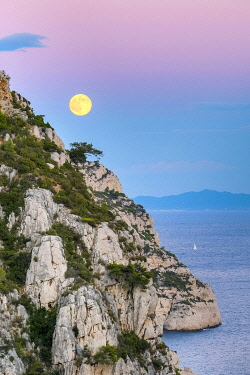 FRA11348AW Full moon rising over ocean and Mediterranean landscape at Calanque de Sugiton after sunset, Parc National des Calanques, Provence-Alpes-Côte d'Azur, Bouches-du-Rhône, France