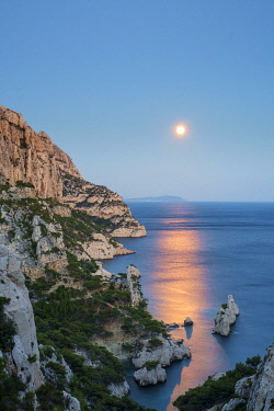 FRA11351AW Full moon rising over ocean and Mediterranean landscape and Calanque de Sugiton at dusk, Parc National des Calanques, Provence-Alpes-Côte d'Azur, Bouches-du-Rhône, France
