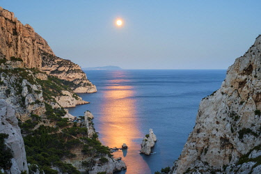 FRA11352AW Full moon rising over ocean and Mediterranean landscape and Calanque de Sugiton at dusk, Parc National des Calanques, Provence-Alpes-Côte d'Azur, Bouches-du-Rhône, France