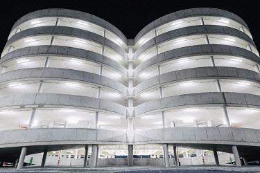 GER11790AW Illuminated parking garage concrete structure at night, Hamburg, Germany