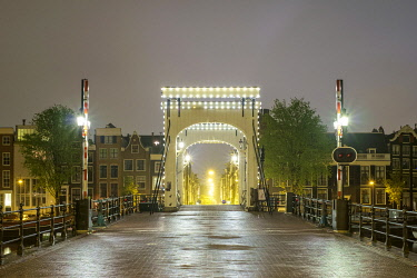 NLD995AWRF Magere Brug illuminated at night on foggy evening, Amsterdam, North Holland, Netherlands