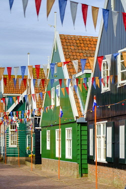 NLD971AW Traditional wooden houses decorated with flags of Dutch national colors for Koningsdag, or King's Day, Marken, North Holland, Netherlands