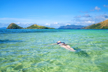 PHI1591AW Woman relaxing in the clear blue water near CYC Island, Coron, Palawan, Philippines. (MR)
