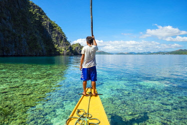 PHI1593AW Filipino boatman navigating through a shallow reef at Hidden Lagoon, Coron Island, Palawan, Philippines