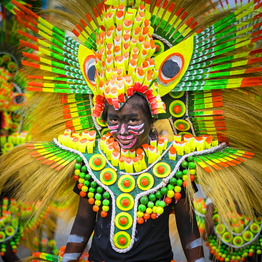 PHI1639AW Kalibo, Aklan, Western Visayas, Philippines. A participant in the Ati-atihan festival wearing brighly-colored hand made costume made from recycled and natural materials. Ati-Atihan festival takes plac...