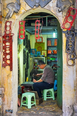 VIT1635AW Vietnamese man working in his shop producing engine gaskets by hand, Hanoi Old Quarter, Hoàn Kiá��m District, Hanoi, Vietnam, Hanoi, Vietnam