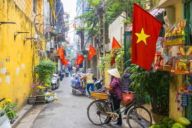 VIT1645AW Woman pusing a bicycle through an alleyway lined with red Vietnamese flags, Hoàn Kiá��m District, Old Quarter, Hanoi, Vietnam