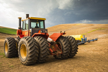 US48AJN0267 USA, Washington State, Palouse, Whitman County. 2015 No Water No Life Snake River Expedition, Pioneer Stock Farm. Approaching storm, tractor used for spraying on chemically fallowed field