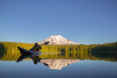 US48GLU1010 USA, Washington State. Woman kayaker paddles on calm, scenic Takhlakh Lake with Mt. Adams in the background (MR).