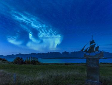 EU14MZW1446 Northern Lights over Eyjafjordur near Dalvik in Iceland. Monument commemorating ship builder Eyvindur Jonsson, Northern Iceland.