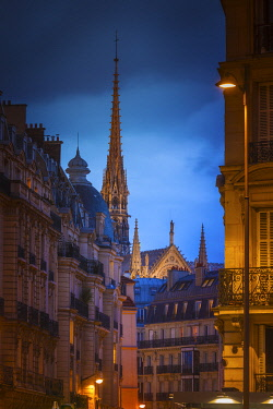 FRA11450AW France, Paris, Notre Dame Cathedral, spire above rooftops at dusk