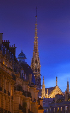 FRA11451AW France, Paris, Notre Dame Cathedral, spire above rooftops at dusk