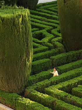 SPA9327AW Spain, Madrid, gardens of the Royal Palace, girl playing in maze (MR)