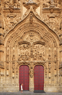 SPA9349AW Spain, Castile and Leon, Salamanca, Woman at facade of cathedral, UNESCO World Heritage site (MR)