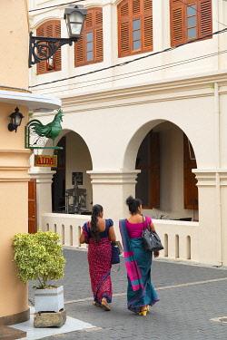 SRI2346AWRF Women walking past The Fort Printers Hotel, Galle, Southern Province, Sri Lanka