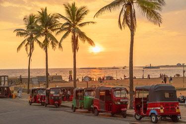 SRI2329AW Tuk tuks parked along Galle Face Green at sunset, Colombo, Sri Lanka