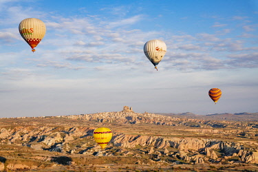 TUR1075AW Uchisar Castle as seen from Goreme, listed as World Heritage by UNESCO, overflight of Cappadocia with multicolored balloons at sunrise. Turkey, Nevsehir