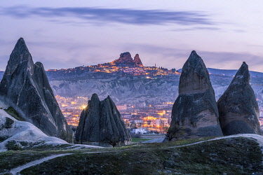 TUR1085AW Turkey, Central Anatolia, Cappadocia. Rose Valley with fairy chimney on foreground, Uchisar Castle and town on background at blue hour. Unesco World Heritage site