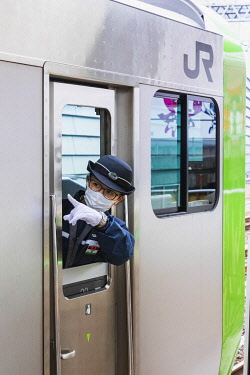 TPX70250 Japan, Honshu, Tokyo, Japan Railways (JR), Female Train Guard Checking Departure Safety