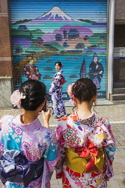 TPX70310 Japan, Honshu, Tokyo, Asakusa, Young Women in Kimono Taking Photos in Front of Shop Shutter depicting Mt.Fuji
