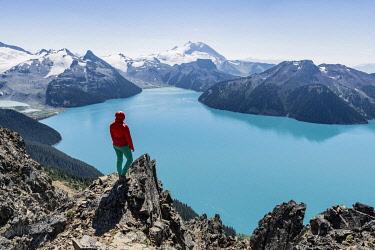 IBXMMW04824618 View from Panorama Ridge Hiking Trail, Hiker on a Rock, Garibaldi Lake, Guard Mountain and Deception Peak, Back Glacier, Garibaldi Provincial Park, British Columbia, Canada, North America