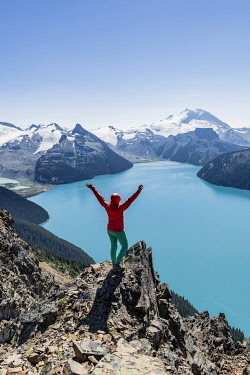IBXMMW04824666 View from Panorama Ridge Hiking Trail, Hiker on a rock stretches arms into the air, Garibaldi Lake, Turquoise Glacial Lake, Guard Mountain and Deception Peak, Glacier, Garibaldi Provincial Park, Briti...