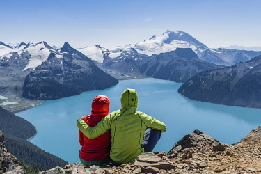 IBXMMW04824671 View from Panorama Ridge trail, Two hikers sitting on a rock with Garibaldi Lake, turquoise glacial lake, Guard Mountain and Deception Peak, Glacier, Garibaldi Provincial Park, British Columbia, Canad...