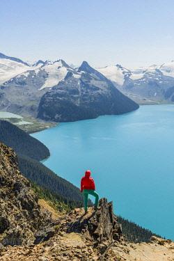 IBXMMW04824740 View from Panorama Ridge Hiking Trail, Hiker on a Rock, Garibaldi Lake, Guard Mountain and Deception Peak, Back Glacier, Garibaldi Provincial Park, British Columbia, Canada, North America