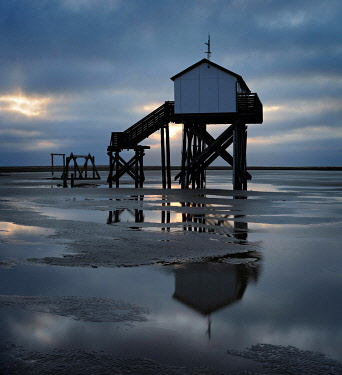 IBXKCV04889140 Lake house at low tide on the beach at dawn, dark clouds, St. Peter-Ording, Schleswig-Holstein Wadden Sea National Park, Schleswig-Holstein, Germany, Europe