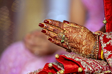 IBXDGB04821655 Traditional bridal jewelry and henna decoration on the hands of the bride during a religious ceremony at a Hindu wedding, Mauritius, Africa