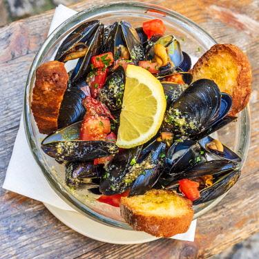 ITA14355AW Europe, Italy, Liguria. Genoa, Boccadasse. A plate of mussels Marinara style.