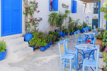 Streetside cafe tables and chairs, Amorgos, Cyclades Islands, Greece, Europe © AWL Images