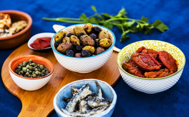 ITA14449 Composition of sun dried and seasoned food from the Mediterranean including Peppered Sund Dried Goats Cheese, Capers, various tyrpes of Olives, Tomato paste; Sundried Tomatoes, Salted Anchovies and al...