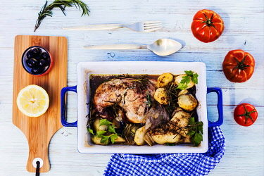 ITA14459 Oven cooked chicken with baked potatoes and herbs served in a dish with cutlery, tomatoes, olives, lemon and rosemary with blue tablecloth.
