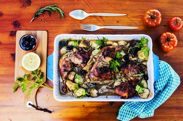 ITA14460 Oven cooked chicken with baked potatoes and herbs served in a dish with cutlery, tomatoes, olives, lemon and rosemary with green tablecloth.